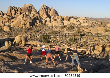 Female hiking team stretches after climbing to  the summit of a challenging rock spire in Joshua Tree National Park. - stock photo
