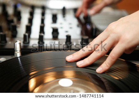 Female hip hop dj scratching vinyl records with music on party in night club.Professional disc jockey girl scratches old analog record with popular tracks.Concert audio equipment on stage