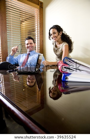 Female Hispanic office worker and male colleague in boardroom with laptop computer