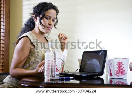 Female Hispanic office worker eating Chinese takeout food for lunch while working on laptop