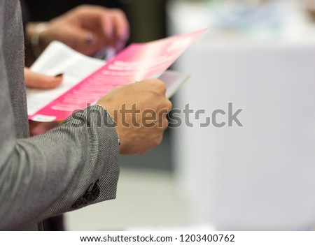 Female holding a leaflet, close up, blurred, space for text, isolated #1203400762