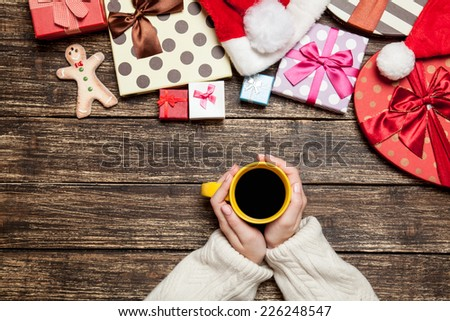 Female holding cup of coffee on wooden table near christmas gifts