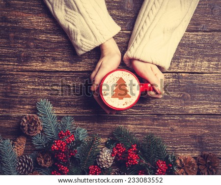 Female holding cup of coffee with cream christmas tree on a table.