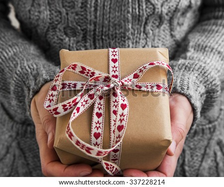 Female Holding Rustic Decorated Christmas Gift with Red and White Ribbon