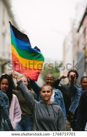 Female holding the gay rainbow flag at the Gay Pride Parade in city. Supporters and members of LGBTQI community during a Queer Pride Parade.