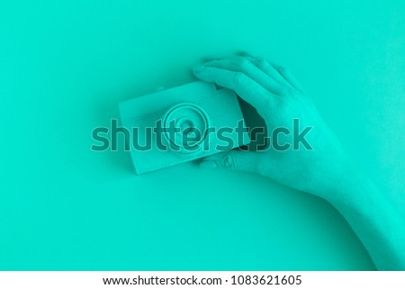 Female holding vintage film photo camera. Turquoise colored minimal abstract creative concept.