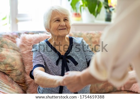 Female home carer supporting old woman to stand up from the sofa at care home Сток-фото ©