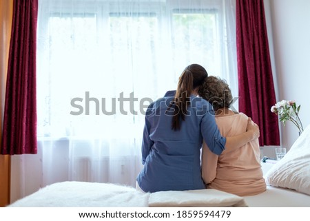 Female Home Nurse Hugging Elderly Woman on Bed. Back View of Female Nurse With Her Arm Around Elderly Patient Shoulder. Stock photo ©