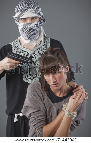 female hostage and hijacker with gun over grey background