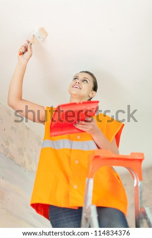 Female house painter paints the ceiling with a brush - stock photo
