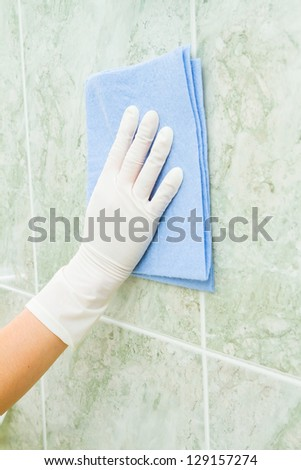 Female household, tile cleaning with rag and gloves
