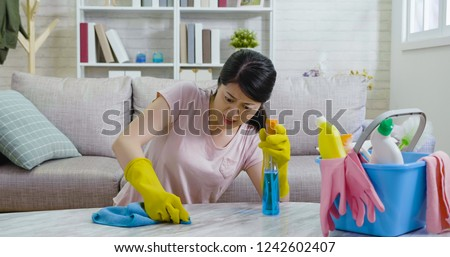 female housekeeper trying hard to remove the dust on the bright marble table in the living room in the morning. young girl in protective gloves doing housework cleaning up her apartment seriously. #1242602407