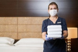 Female housemaid holding clean folded towels in bed room