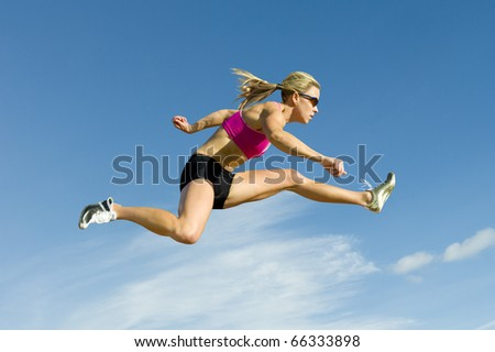 Female hurdler jumps against a blue sky in the background.