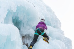 Female ice climber climbing up the side of an icy slope with bumps, ridges, and icicles