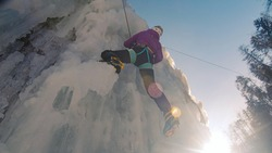 Female ice climber in triangle-shaped form pulling the top safety rope, climbing up the side of an icy slope with bumps, ridges, and icicles