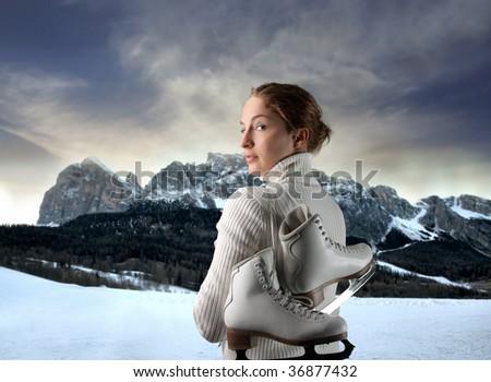 female ice skater portrait against a mountain landscape - stock photo