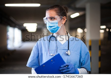 Female ICU doctor in hospital parking lot,first responder frontline key medical worker,holding clipboard patient medical card,looking away,emergency service during COVID-19 coronavirus pandemic crisis