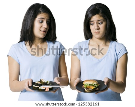 Female identical twins looking down on the other's choice of food