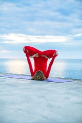 female in a red yoga suit makes a headstand asana on a yoga mat near a sea, blue clouds on the horizon