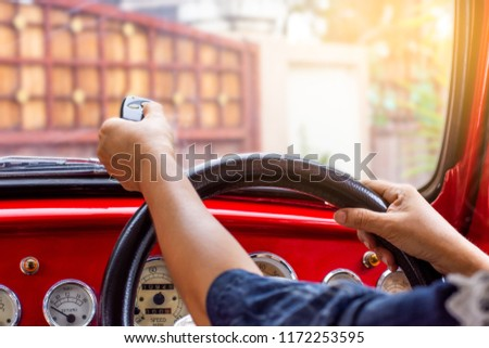 Female in red car, hand holding and using remote control to open the automatic gate while leaving home. Security and save time concept.