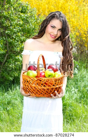 Female in white dress presents basket of apples