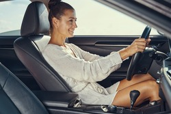 Female in white tunic at the wheel of automobile