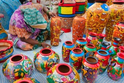 Female Indian artist painting colorful terracotta pots, works of handicraft, for sale during Handicraft Fair in Kolkata.
