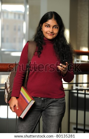Female Indian student holding book and cellphone indoors