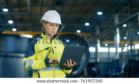 Female Industrial Engineer in the Hard Hat Uses Laptop Computer while Standing in the Heavy Industry Manufacturing Factory. In the Background Various Metalwork Project Parts Lying #761907340