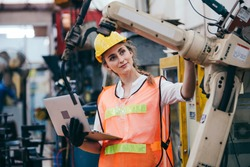 Female industrial engineer or technician worker in hard helmet and uniform using laptop checking on robotic arm machine. woman work hard in heavy technology invention industry manufacturing factory