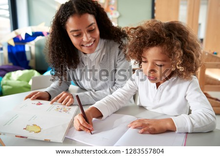 Female infant school teacher working one on one with a young schoolgirl sitting at a table writing in a classroom, front view, close up