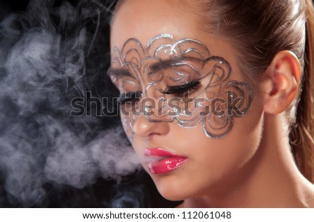 Female inhale smoke from cigarette on dark area