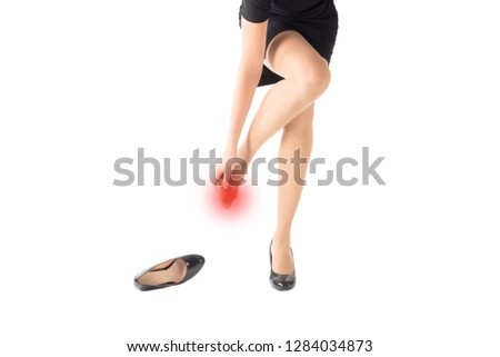 Female injured and rubbed toes by high heels tight shoes, isolated on white. Red pain marker. Woman takes off a shoe and holds her sore spot. Medical and healthcare concept