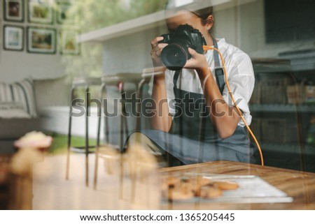 Female inside a kitchen taking pictures of pastries on table with dslr camera. Female chef wearing apron taking pictures of fresh baked dishes.