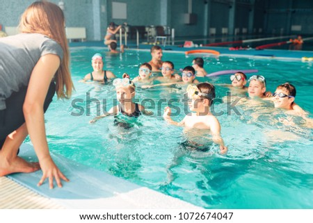 Female instructor teaches children how to swim. Kids with goggles in water listening trainer. Happy kids in modern sport center. Concept of fun, leisure and recreation. Stockfoto ©
