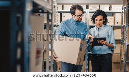 Female Inventory Manager Shows Digital Tablet Information to a Worker Holding Cardboard Box, They Talk and Do Work. In the Background Stock of Parcels with Products Ready for Shipment.