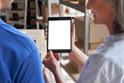 Female inventory warehouse manager holding in hands using digital tablet computer smart data technology mock up blank white screen talking to courier holding retail boxes. Over shoulder closeup view.