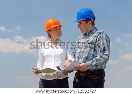 Female investor and site manager discussing building plans over blue sky