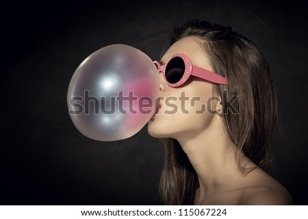 female is  blowing a big bubble with her gum