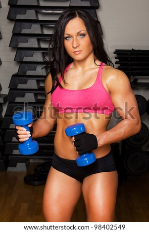 Female is doing exercise with weights