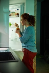 Female is standing in front of refridgerator and trying meal from jar at night