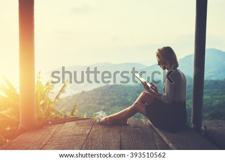 Female is typing something in diary on touch pad, while is sitting against amazing Asian landscape in beautiful summer evening. Woman is watching video on digital tablet during her trip in Thailand #393510562