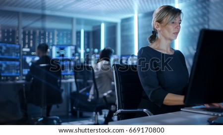 Female IT Engineer Works on Her Desktop Computer in Government Surveillance Agency. In the Background People at Their Workstations with Multiple Screens Showing Graphics. #669170800
