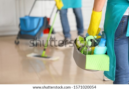 Female janitor with cleaning supplies in kitchen
