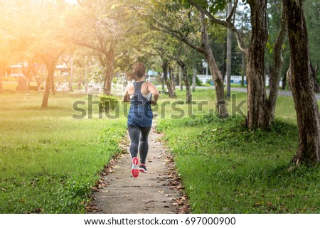 Female jogger.a healthy outdoor lifestyle.young fitness woman running on the road in the morning. #697000900