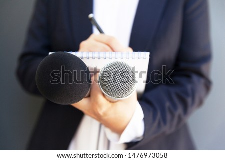 Female journalist at news conference or media event, writing notes, holding microphone #1476973058