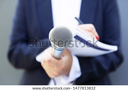 Female journalist at news conference or media event, writing notes, holding microphone #1477813832