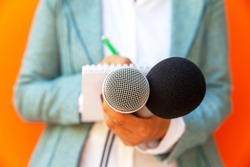 Female journalist at news conference or media event, writing notes, holding microphone. Journalism concept.