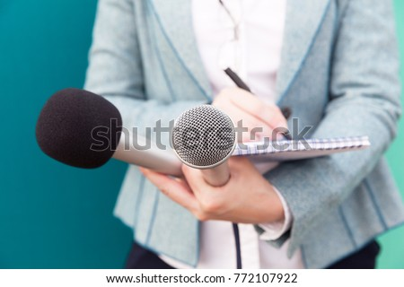 Female journalist at news conference, writing notes, holding microphone #772107922